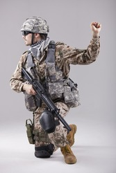 armed soldier kneeling with hand warning or stop gesture