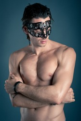 Portrait of young man shirtless with mask against dark background.