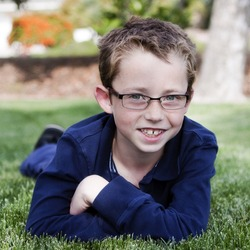handsome young boy in glasses smiling as he lies in the grass