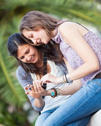 Two Beautiful Women Sending Messages with Mobile