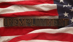 the word unemployment on an old USA flag