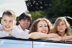 A family of four sits in a cabriolet, parents smile and look into the camera, children look the other way.