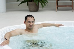 Young handsome man in indoor jacuzzi on resort