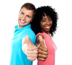 Smiling trendy couple showing thumbs up against white background