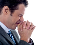 Business executive praying to god after business disappointment