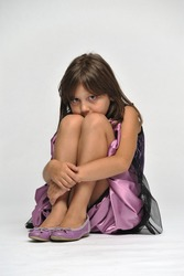 Young girl sitting on the floor sideways hiding her face behind her knees