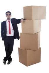 Young businessman standing near cardboard boxes, can be used as symbol of success exporter