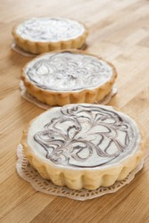 Three white chocolate cheesecake tarts on a wood counter