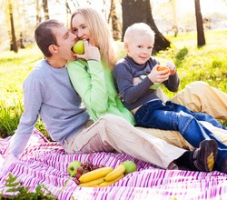 happy young family having a picnic in the park on a summer day