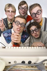 Five nerdy guys sitting in front of old-fashioned keyboard. They are looking at camera. One of them is holding joystick. Front view