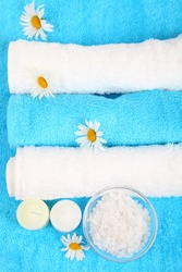 Beautiful spa setting with daisies, salt and towels
