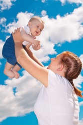 Young mother raising up her baby boy into the air