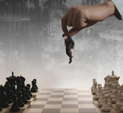 A boss uses as a pawn a businessman in a chessboard