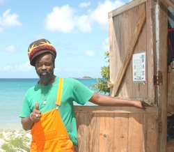 native rasta man by Caribbean Sea with thumbs up positive hand sign in Carriacou Grenada Grenadine Island