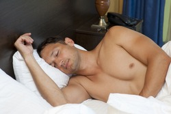 Portrait of a shirtless young man sleeping on the bed at home - Indoor