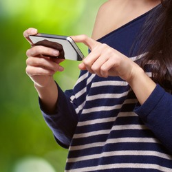 portrait of a young woman touching a modern mobile against a nature background