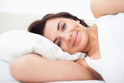Smiling woman lying while waking up in her bedroom
