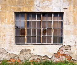 A large window with broken panes on the wall of a dilapidated old building