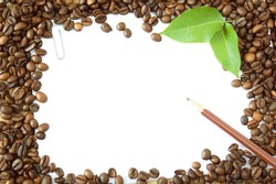 Coffee beans background with wooden pen, fresh green leaves and white blank