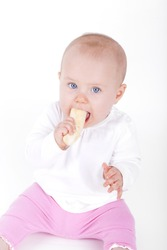 studio shot of a 7 month old baby girl eating a banana