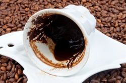 Empty cup of black coffee with coffee sediment, traditionally using for fortune telling, with copy-space on the coffee beans