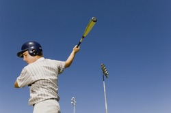 Young baseball player swinging bat against blue sky