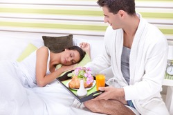 Portrait of happy young man serving breakfast for his girlfriend in bed at home