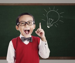 Portrait of male elementary school student with lightbulb picture on blackboard