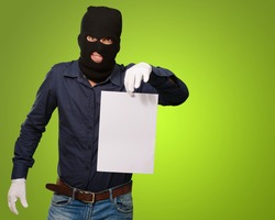 Burglar In Face Mask On Green Background