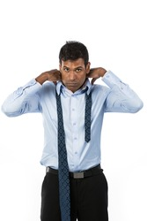Indian business man putting on his tie. The isolated white background