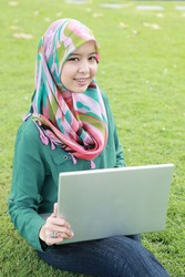 Portrait of young pretty Asian Muslim college girl with laptop and smile