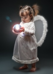 Little girl dressed as angel holding Christmas ornament