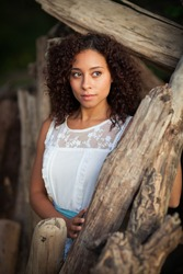 A beautiful, young black woman poses  by driftwood.