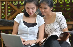 Two pretty college girls studying, learning and sharing information they found on a laptop and a book or magazine with happy expression at outdoor scene.