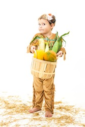 adorable little boy dressed as a Native American holding a basket of harvest vegetables