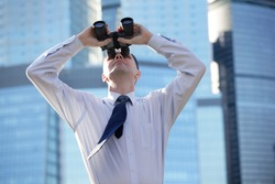 Businessman with binoculars against modern office buildings