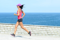 Fitness girl running fast on summer day with sea on background. Beautiful female athlete exercising.