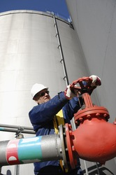 industry worker turning on pipeline and fuel pump inside oil industry
