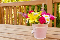 Flowers from the garden in pink bucket vase