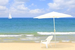 White beach umbrella and chair on the Mediterranean sandy beach