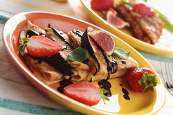 Strawberry crepes with chocolate syrup, figs and mint on the table