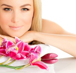 Closeup portrait of attractive female in spa with pink orchid flower, pretty woman with luxury natural makeup, good looking girl, beauty treatment, aromatherapy, health care, zen balance concept