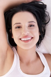 Happy sensual young woman lying in bed and smiling to camera