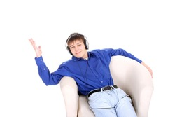 happy teenager in headphones sitting in a chair on the white background