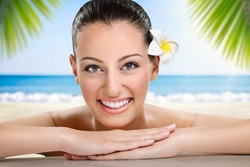 Beautiful spa woman smiling, health and beauty, against the beach