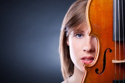 Portrait of young and beautiful woman with a violin