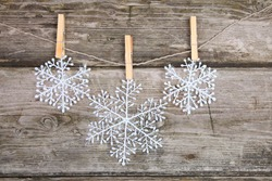 Christmas decorations (snowflake) hanging over wooden background