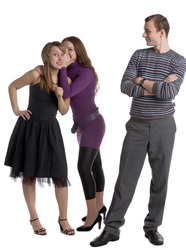 two young women whispering about a man standing before them isolated on white