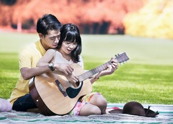 Portrait of romantic young couple playing a guitar in the park on autumn day