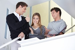 Man with woman at floorlayer office holding his thumbs up